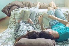Couplez le mensonge sur le plancher et la lecture gentille de levage de jambes Photo libre de droits