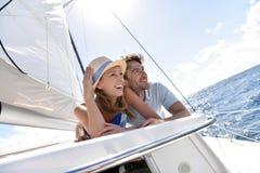 Couplez le mensonge sur un bateau à voile ayant l'amusement photo stock