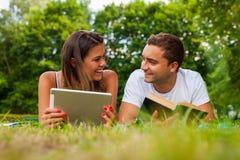 Couplez le mensonge sur une herbe avec le comprimé et le livre Image libre de droits