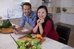 Couplez le penchement sur le plan de travail de cuisine avec des légumes dans l'avant Photos stock