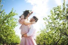 Couplez le portrait d'une fille et d'un type recherchant une robe de mariage, un vol rose de robe avec une guirlande des fleurs s Images stock