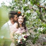 Couplez le portrait d'une fille et d'un type recherchant une robe de mariage, un vol rose de robe avec une guirlande des fleurs s Photos stock