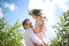 Couplez le portrait d'une fille et d'un type recherchant une robe de mariage, un vol rose de robe avec une guirlande des fleurs s Image stock