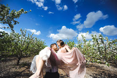 Couplez le portrait d'une fille et d'un type recherchant une robe de mariage, un vol rose de robe avec une guirlande des fleurs s Images libres de droits