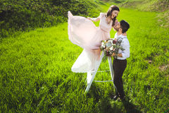 Couplez le portrait d'une fille et d'un type recherchant une robe de mariage, un vol rose de robe avec une guirlande des fleurs s Photo stock