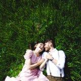 Couplez le portrait d'une fille et d'un type recherchant une robe de mariage, un vol rose de robe avec une guirlande des fleurs s Photo libre de droits