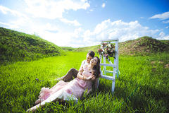 Couplez le portrait d'une fille et d'un type recherchant une robe de mariage, un vol rose de robe avec une guirlande des fleurs s Image libre de droits