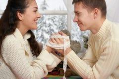 Couplez le portrait près de la fenêtre avec la saison d'hiver, habillée dans le blanc, le plan rapproché de visage, l'amour et le Photographie stock libre de droits