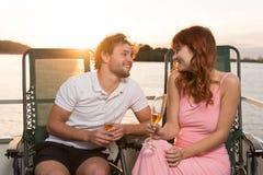 Couplez le regard beau sur l'un l'autre pendant le coucher du soleil sur le yacht photos libres de droits