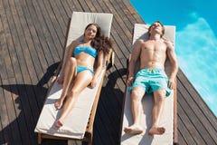 Couplez le repos sur des canapés du soleil par la piscine Photos libres de droits