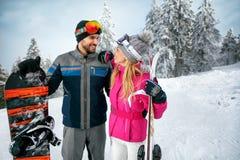 Couplez le ski et le snowboarding appréciant dans le toget neigeux de montagnes Photos libres de droits