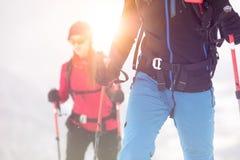 Couplez le skieur d'homme et de femme explorant la terre neigeuse marchant et skiant avec le ski alpin Alpes de l'Europe Jour ens images libres de droits
