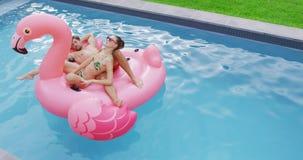 Couplez le sommeil ensemble sur le tube gonflable dans la piscine 4k banque de vidéos