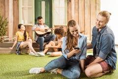 Couplez le sourire et à l'aide du smartphone tandis que leurs amis jouant la guitare derrière Images libres de droits