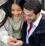 Couplez le sourire et regarder le message au téléphone portable ensemble Image stock