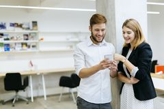Couplez le sourire tout en regardant le téléphone dans le bureau image stock