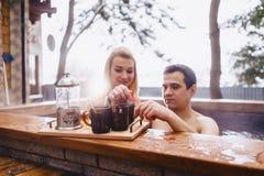 Couplez le thé chaud potable tout en se reposant pendant l'hiver en dehors de chaud photographie stock libre de droits