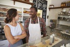 Couplez le travail à une barre de sandwich regardant l'un l'autre photographie stock libre de droits