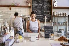 Couplez le travail derrière le compteur à un café photos stock