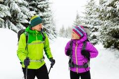 Couplez le trekking de randonneurs sur la neige en bois d'hiver Photos libres de droits