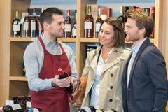 Couplez le vin de bouteille d'achats dans le magasin photo stock