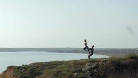 Couplez le yoga de pratique d'acro à la nature, fille avec des bras augmentés sur une jambe équilibre dessus paye de son associé  clips vidéos