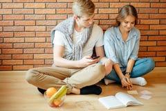 Couplez les étudiants s'asseyant en dehors de la salle de classe et étudiant ensemble Photographie stock