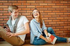 Couplez les étudiants s'asseyant en dehors de la salle de classe et étudiant ensemble Images stock