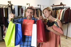 Couplez les achats avec l'homme fatigué et ennuyé en tenant les sacs et la robe de recherche heureuse de femme photo stock