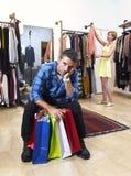 Couplez les achats avec l'homme fatigué et ennuyé en tenant les sacs et la robe de recherche heureuse de femme image stock