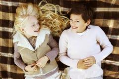 Couplez les adolescents se trouvant sur le plaid ayant l'amusement Photographie stock libre de droits