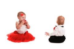 Couplez les bébés de fille et de garçon jouant avec la valentine de concept de coeurs Photo stock