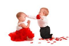 Couplez les bébés de fille et de garçon jouant avec la valentine de concept de coeurs Photographie stock