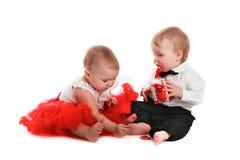 Couplez les bébés de fille et de garçon jouant avec la valentine de concept de coeurs Photos libres de droits