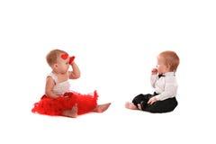 Couplez les bébés de fille et de garçon jouant avec la valentine de concept de coeurs Photo libre de droits