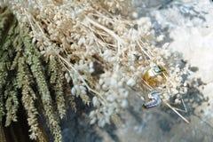 Couplez les bagues à diamant accrochant sur le bouquet sec de fleurs, pour l'amour Photo libre de droits
