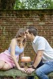 Couplez les baisers au-dessus du gâteau célébrant un anniversaire d'an photos stock