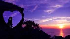 Couplez les baisers dans une pierre en forme de coeur sur une montagne avec le coucher du soleil pourpre de ciel Image stock