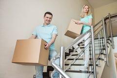 Couplez les boîtes en carton de transport tout en abaissant des étapes à la nouvelle maison Image stock