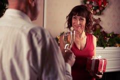 Couplez les cannelures de champagne tintantes devant le décor de cheminée Image libre de droits