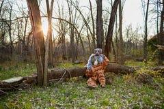Couplez les costumes impairs de port de peluche se reposant par l'arbre Photographie stock