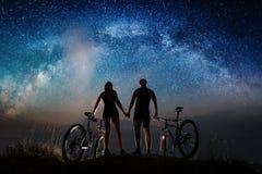 Couplez les cyclistes avec des vélos de montagne la nuit sous le ciel étoilé Images libres de droits