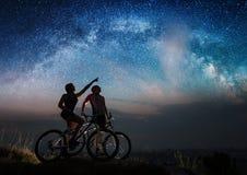 Couplez les cyclistes avec des vélos de montagne la nuit sous le ciel étoilé Photo stock