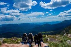 Couplez les jambes sur la crête de la colline regardant sur les montagnes et le beau ciel dans le jour d'été, la première vue de  Image stock