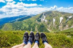 Couplez les jambes sur la crête de la colline regardant sur les montagnes et le beau ciel dans le jour d'été, la première vue de  Photos libres de droits