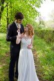 Couplez les jeunes mariés marchant en parc montrant la plupart de beau Image libre de droits