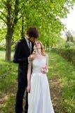 Couplez les jeunes mariés marchant en parc montrant la plupart de beau Photographie stock