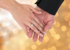 Couplez les mains avec des fiançailles de mariage d'anneau avec le fond clair de scintillement de bokeh Photographie stock libre de droits