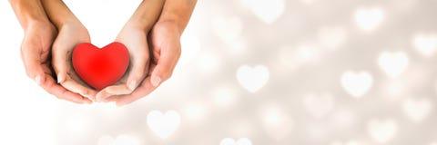Couplez les mains du ` s tenant le coeur ainsi que des coeurs de transition d'amour du ` s de valentine Photos libres de droits