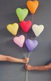 Couplez les mains tenant la forme multicolore de coeur de ballons sur le CCB gris Images libres de droits